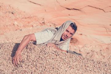 male model posing in a rocky desert