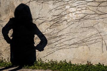 Ombra di figura di donna proiettata su un vecchio muro