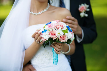 Bright colorful wedding bouquet in hands of the bride
