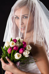 portrait of a bride with a bouquet of tulips with a veil