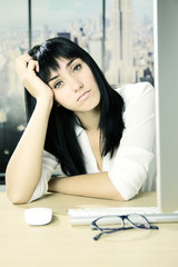 Cute young sad business woman in office looking camera