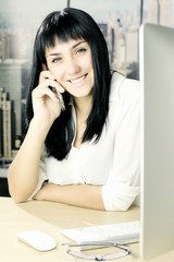 Happy young business woman on the phone in office