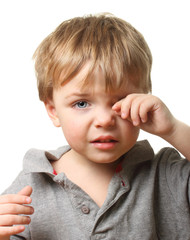 Sad child wiping tears.