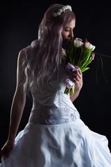 woman in wedding dress smelling wedding bouquet