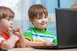 happy children looking at laptop