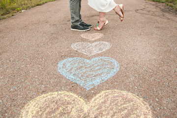Heart symbols shaped on ground and legs of two people in love