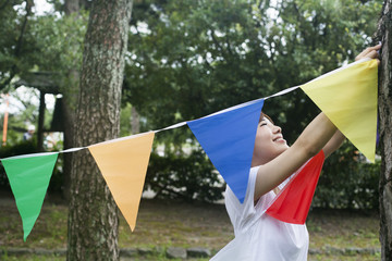 A woman in a Kyoto park holding up a colourful row of flags.
