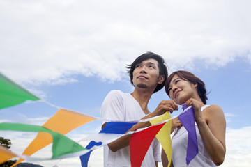 A couple, a man and woman in a Kyoto park holding up a colourful row of flags.