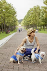 Woman walking two dogs on a paved path.