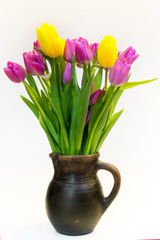 Bouquet of violet and yellow tulips in an old clay pot