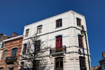 Immeuble blanc en coin de rue, ciel bleu, Bruxelles