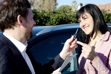 Woman getting keys of new car from salesman