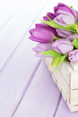 Purple tulips box over wooden table
