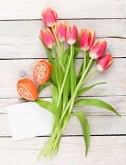 Colorful tulip bouquet, easter eggs and blank greeting card