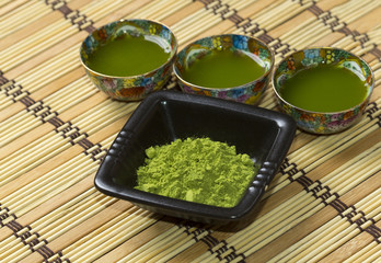 Green matcha in a small ornamented cups and black plate
