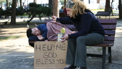 Homeless, sick family begging on a park bench