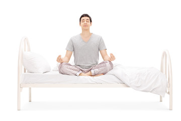 Calm guy meditating seated on bed