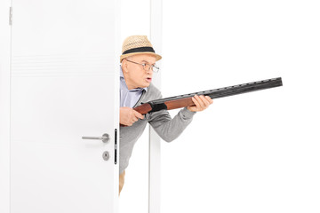 Angry senior with a rifle walking through a door