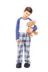 Full length portrait of a sleepy boy holding a teddy bear