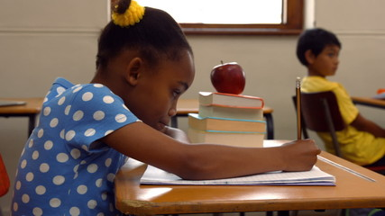Schoolchild writing in notepad at school