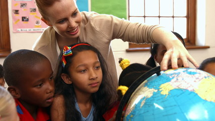 Teacher looking at globe with pupils