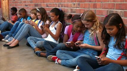 Schoolchildren sitting outside using phones