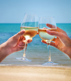 Man and woman clanging wine glasses with white wine at sea backg poster