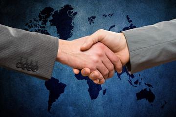 Handshake between business men against world map