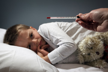 Sick child in bed with high temperature