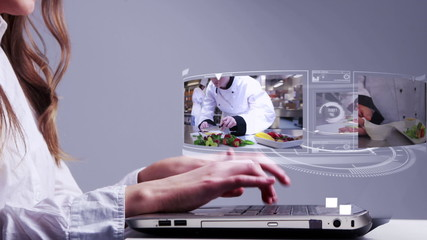 Woman using laptop with cooking holographic interface