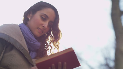 Reveal to woman reading a book outdoors on a bright day
