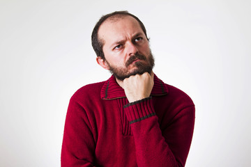 Man in red sweater, with beard and mustaches in thinking pose