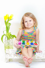 Two years old girl holding Easter eggs carton
