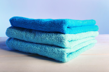 Folded towels on wooden table and light colorful background