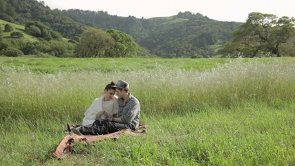 Young couple sitting on a blanket holding hands in nature