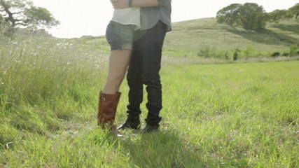 Side view of a young couple standing on a grass field hugging