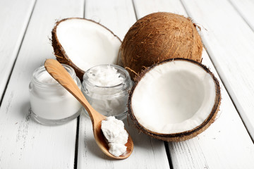 Coconut with jars of coconut oil and cosmetic cream