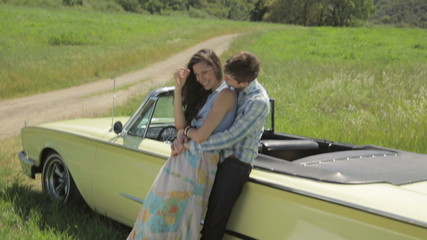 Young couple leaning on vintage convertible hugging