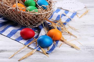 Easter eggs in basket on vintage wooden planks background