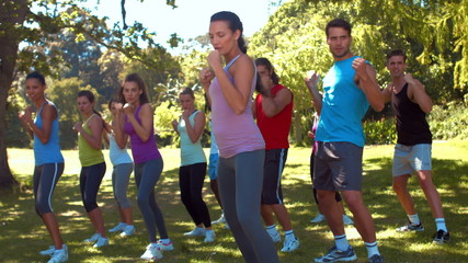 In high quality format fitness group working out in park