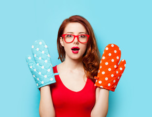 Surprised redhead girl with oven gloves
