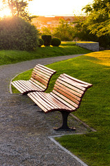 Two wooden benches in the park at dusk