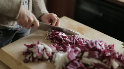 Woman chopping fresh red cabbage on a wooden table in kitchen