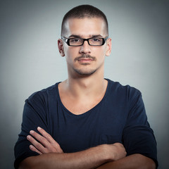 Portrait of serious young man wearing glasses