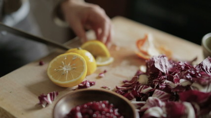 Close up of woman slicing lemon on a wooden table in kitchen