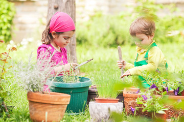 Two cute little children gardening in front or back yard