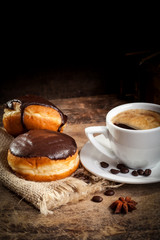 Donuts with coffee cup served on wooden table