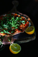 Flatbread with minced meat and bell peppers, arugula and lemon