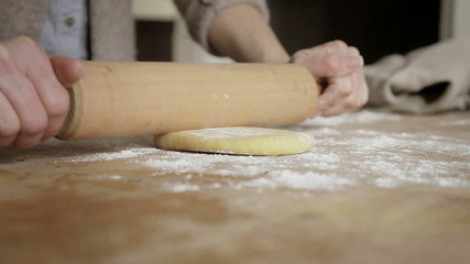 Woman rolling out dough on a cutting board while making pasta