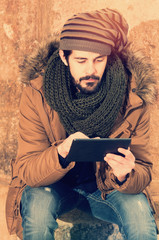 stylish hipster man sitting using tablet with a warm tone filter